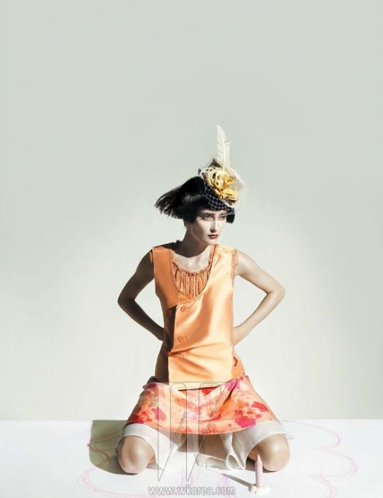 화사한 오렌지 톤의 실크 베스트와 톱, 스커트는 모두 Louis Vuitton, 모자는 Stephen Jones 제품.