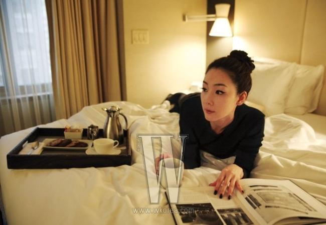 february 10th am 11:15호텔 침실 위의 그녀가 입은 검정 드레스, 창가 테이블 위의 그녀가 입은 검정 저지 소재 톱과 이너로 매치한 흰 셔츠, 엘리베이터 앞에 선 그녀가 입고 있는 파랑 실크 소재의 미니 드레스는 모두 Kuho 제품.