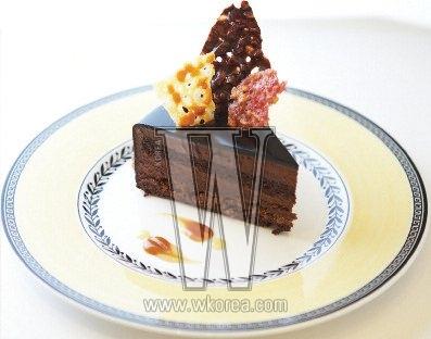 발로나 초콜릿으로 코팅한 쇼콜라 케이크 안에는 부드러운 초코 무스와 바삭한 휘앙틴이 함께 들어 있어 두 가지 식감을 한 번에 느끼는 재미가 있다. 위에 꽂힌 세 종류의 누가틴 역시고소하고 또한 달콤하다.