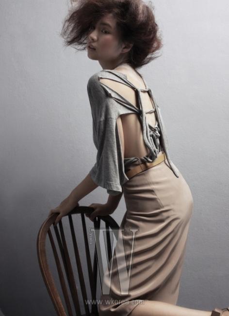 해체적인 등 장식의 티셔츠는 Maison Martin Margiela, 무릎 길이의 새틴 스커트와 캐멀색 벨트는 Celine,