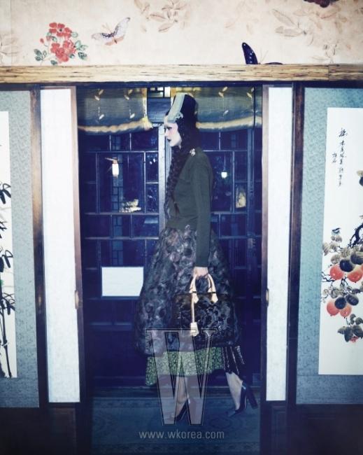 누빔 사이로 깃털을 넣은 풍성한 서클 플레어 스커트, 어깨에 크리스털을 장식한 초록 니트, 리본 장식의 펌프스와 스피디 백은 모두 Louis Vuitton 제품. 머리에 쓴 탕건과 놋쇠 머리 장식은 Damyeon by lee hye soon, 탕건 위의 노리개는 Tchai 제품.