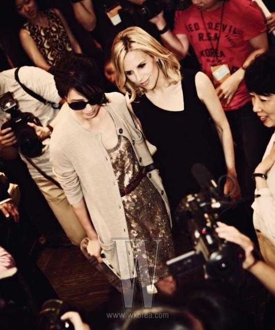 김희애가 입은 오트밀 색상의 카디건, 금빛 스팽글 장식의 미니 드레스, 대담한 사이즈의 선글라스, 스웨이드 소재의 오버사이즈 클러치는 모두 Tory Burch 제품.