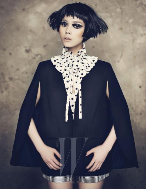 프릴 장식의 하이 네크라인이 돋보이는 블라우스는 Kate Spade, 소매에 슬릿을 낸 독특한 구조의 케이프 재킷은 Lewitt 제품. 줄무늬 반바지는 스타일리스트 소장품.