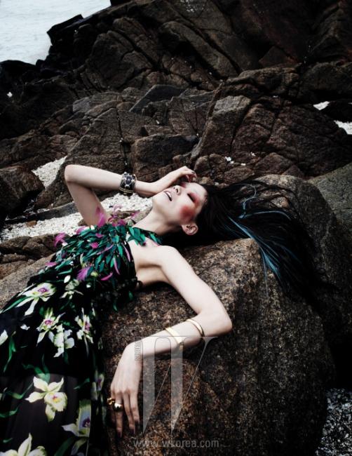 시퀸과 깃털이 화려하게 장식된 시폰 드레스는 Dior, 왼팔에 착용한 뱅글과 중지에 착용한 반지는 모두 CK Calvin Klein, 검지에 착용한 반지는 H.R., 오른팔에 착용한 볼드한 뱅글은 Chanel 제품.
