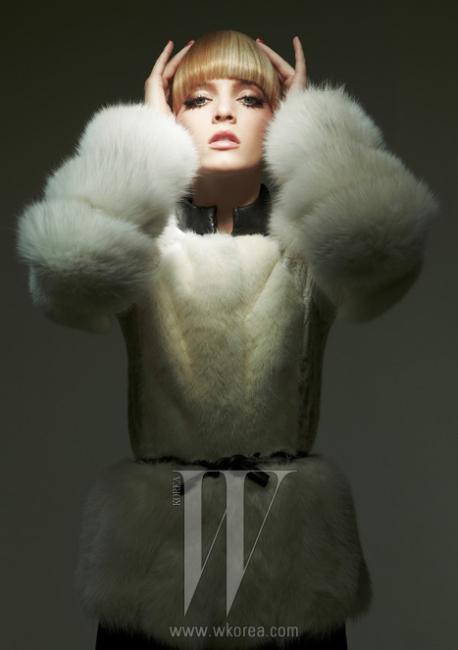 볼룸감이 넘치는 소매, 검정 가죽 칼라가 특징인 화이트 퍼 재킷과 리본으로 묶어 연출한 가죽 벨트는 모두 Burberry Prorsum 제품.