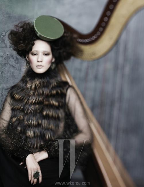 시스루 레이스 소재의 소매가 돋보이는 검정 드레스와 앞판의 퍼 장식은 Fendi 제품. 라임색 원형 모자는 Due Filo, 볼드한 귀고리는 Jamie & Bell, 짙은 푸른색 스톤이 세팅된 반지는 Dblume 제품.