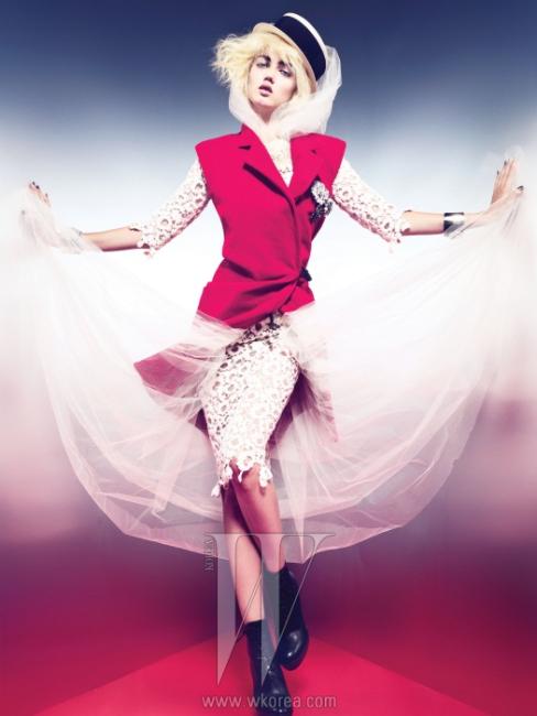 섬세한 레이스로 이루어진 크루즈 컬렉션 드레스와 넓은 검정 테이프로 테두리를 두른 라피아 햇, 베스트에 붙인 브로치 중 아래의 두 개, 손목의 커프스는 모두 Chanel 제품. 왼쪽 가슴에 붙인 브로치 중 가장 위의 카멜리아 브로치는 Chanel Fine Jewelry, 빨강 베스트는 Derek Lam, 앵클부츠는 Gianvitto Rossi for Altuzarra 제품.