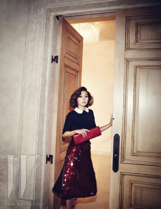 송해나가 든 시선을 사로잡는 빨간색 악어가죽 클러치는 MCM 제품. 심플한 니트 톱과 동그란 칼라 장식, 시퀸처럼 보이는 투명한 플라스틱 조각이 이어진 스커트는 모두 Louis Vuitton 제품.