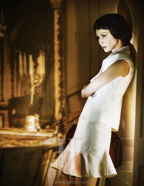 밑부분이 우아하게 퍼지는 튜브 드레스, 슬리브리스 재킷, 로맨틱한 목걸이와 블레이슬릿, 볼드한 아티링은 모두 Yves Saint Laurent 제품.