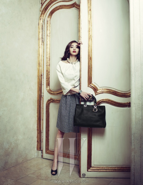 둥그런 어깨선의 곡선미가 우아한 재킷과 체크 스커트, 진주 목걸이, 이브닝 룩에도 제격인 라 디 드 디올(La D de DIOR) 워치, 로고를 딴 참 장식의 디올리시모 백, 미스 디올 슈즈는 모두 Dior 제품.