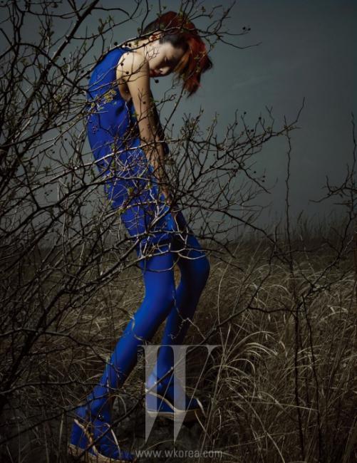 앞은 실크, 뒤는 니트로 이루어진 비대칭 실루엣의 미니 드레스는 Hermes, 구조적인 디자인의 은색 목걸이는 Calvin Klein Watch & Jewelry, 파란색 스웨이드 소재와 스트로 소재가 어우러진 웨지힐 샌들은 Manas 제품.