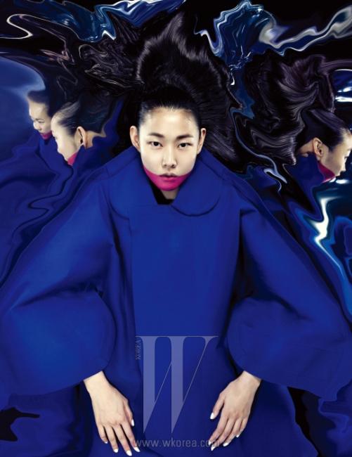 둥그런 칼라와 거대한 볼륨의 소매가 특징인 파란 펠트 소재 코트는 Comme des Garcons 제품.