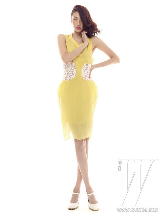 구조적인 커팅이 들어간 안감,센슈얼한 허리의 레이스가 특징인 밝은노란색 슬리브리스 드레스와펀칭 장식의 메리제인 슈즈는모두 Jain Song 제품.