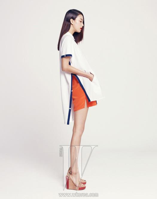 옆선을 단추로 여미는 큼직한판초 스타일의 독특한 피케 셔츠,오렌지색 실크 소재 쇼츠, 베이지와오렌지색이 그래픽적으로 배색된 웨지힐샌들은 모두 Studio K 제품.