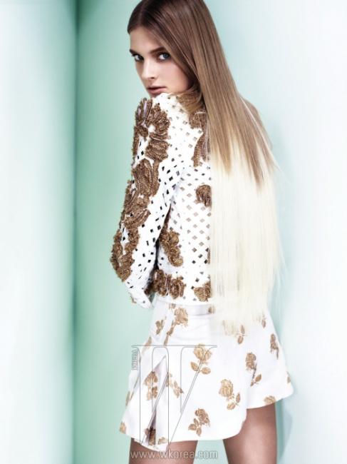 금빛 엠브로이더리 장식이 포인트인흰색 격자 위빙 재킷,금색 실로 장미꽃을 수놓은플레어 쇼츠는 모두 Chanel 제품.