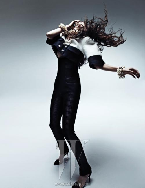검정과 흰색으로구성된 동그란 어깨의 크롭트 재킷,허리선이 높은 검은색 스키니 팬츠,발등 부분에 투명한 PVC 소재를덧댄 검은색 포인티드 토 펌프스와다양한 크기로 구성한 진주 뱅글,목걸이는 모두 Chanel 제품.