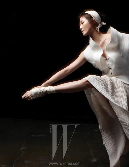 스커트로 연출한 옅은 베이지색의 플리츠 드레스는 Andy & Debb,건축적인 율동감이 느껴지는흰색 베스트는 Giorgio Armani 제품.