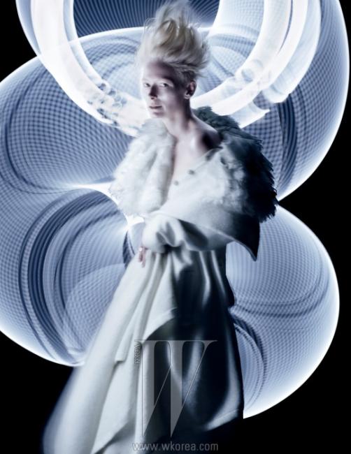 레이스와 깃털이 겹겹이 장식된케이프와 아름다운 단추가 달린 니트드레스는 파리-에딘버러 컬렉션으로Chanel 제품. 흰색 맥시 스커트는Gareth Pugh, 흰색 코트는Ann Demeulemeester,흰색 쿼츠 반지는 Pomelatto 제품.