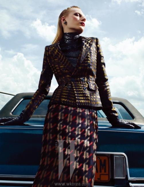 잘록한 허리를 강조하는 하운즈투스 체크무늬 실크 블레이저, 안에 입은 검은색 파이톤 소재 톱, 블레이저와 같은 시리즈로 선보인 미디스커트, 느슨하게 주름을 잡아 착용한검은색 파이톤 소재 장갑은 모두 Gucci 제품.