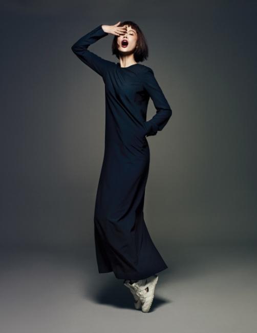 발목까지 부드럽게 떨어지는 긴 소매의 검은색 맥시 드레스와 스포티한 슈즈는 Jain Song 제품.