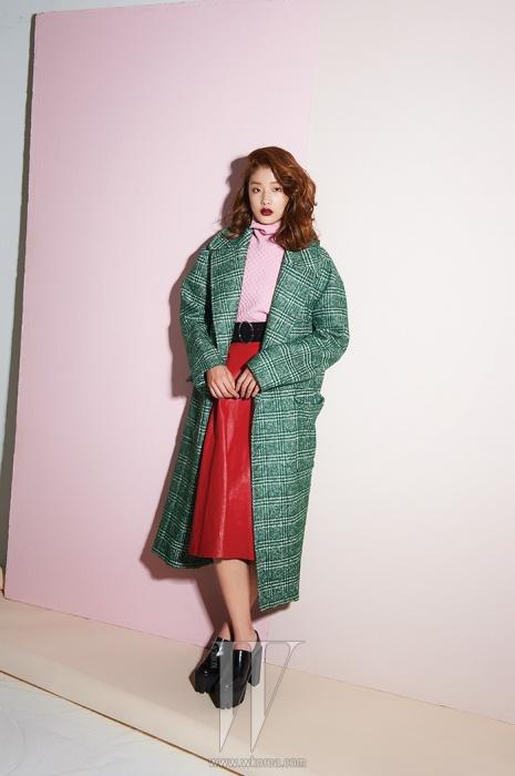 건클럽 체크 패턴의 오버사이즈 코트는 Jardin de Chouette, 안에 입은 핑크색니트 톱은 Eudon Choi, 붉은색 가죽 플레어스커트와 검정 벨트는 Prada, 투박한 플랫폼 슈즈는 Stella McCartney 제품.