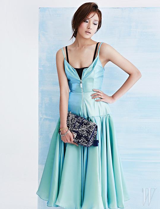 최아라가 입은 집업 장식의 메탈릭 새틴 드레스와 니트 소재의 검은색 브라톱, 그리고 체크 패턴의 '하운즈트위드 트위드' 미스 디올 백은 모두 Dior, 아카이브의 카나주 패턴에서 영감을 얻은 옐로와 핑크 골드의 마이 디올 반지, 옐로 골드의 마이 디올 팔찌는 모두 Dior Fine Jewelry 제품.
