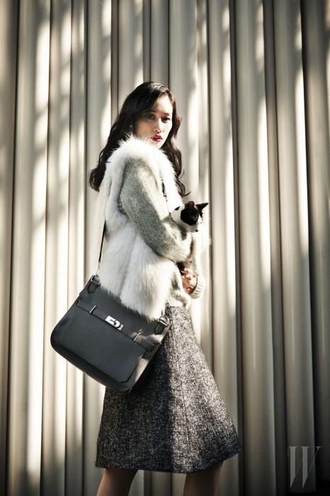 앙고라 소재의 포근한 니트 스웨터는 3.1 Phillip Lim, 밍크 퍼 베스트는 Jill Stuart, 도톰한 울 소재 스커트는 Dolce & Gabbana, 버클 장식 숄더백은 Hermes 제품.
