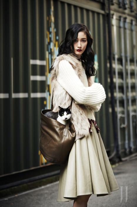 굵은 짜임이 돋보이는 스웨터는 Celine, 안에 입은 하트 프린트의 자줏빛 블라우스는 Burberry Prorsum, 은은한 색감이 고급스러운 폭스 캐시미어 퍼 베스트는 Ds Furs, 풍성한 주름의 드라마틱한 스커트는 Sy=z, 로고 장식의 캐주얼한 크로스백은 See by Chloé 제품.