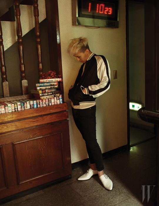 광택이 흐르는 베이스볼 점퍼와 검은색 팬츠, 흰색 슈즈는 모두 Saint Laurent '14 S/S Collection 제품.