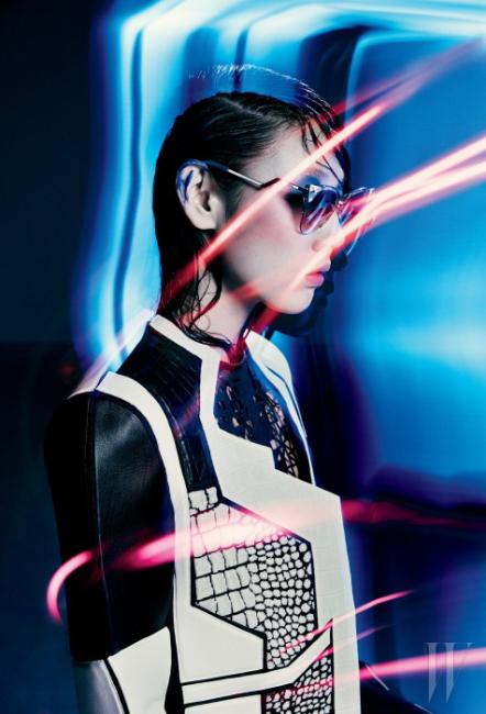검은색과 흰색 가죽을 그래픽적으로 커팅한 구조적인 볼륨의 재킷, 안에 입은 정교한 레이저 커팅의 검정 가죽 드레스, 큼직한 크리스털이 장식된 선글라스는 모두 Fendi 제품.