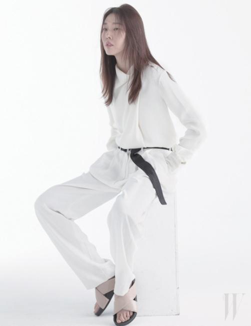 흰색 실크 블라우스와 검정 벨트가 매치된 팬츠, 그리고 베이지색 슬리퍼는 모두 Celine 제품.
