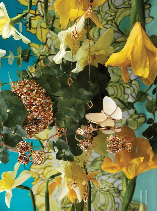 핑크와 화이트 골드 소재를 바탕으로 122.47캐럿의 가닛과 9.90캐럿의 페리도트, 그리고 3.82캐럿의 다이아몬드가 장식된 플라워 모티프 브로치는 Bulgari, 기하학적인 형태의 연꽃 모티프가 여성스러우면서 모던한 분위기를 풍기는 임페리얼 컬렉션의 자수정 반지와 길게 늘어뜨려 우아하게 연출할 수 있는 로즈 골드 소재 목걸이는 Chopard, 로즈 골드 소재에 1.22캐럿 다이아몬드가 세팅되었으며 희망과 행운을 상징하는 두 마리의 나비가 입체적으로 표현된 르 레브 반지는 Lucie, 크림 색상의 화이트 마더오브펄 소재가 우아한 분위기를 더하는 버터플라이 클립은 Van Cleef&Arpels, 꿀벌을 모티프로 옐로와 오렌지 사파이어가 다이아몬드와 함께 어우러진 옐로 골드 소재의 비 마이 러브 귀고리는 Chaumet 제품. 배경으로 연출한 화사한 꽃 프린트의 실크 스카프는 Dior 제품.