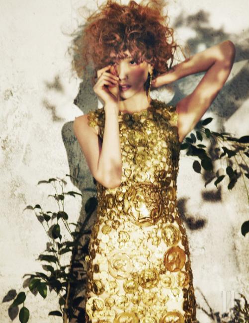 황제의 얼굴이 새겨진 시칠리아의 고대 동전을 모티프로 한 금빛 메탈릭 장식의 미니 드레스와 대담한 크기의 금빛 귀고리는 Dolce & Gabbana 제품.