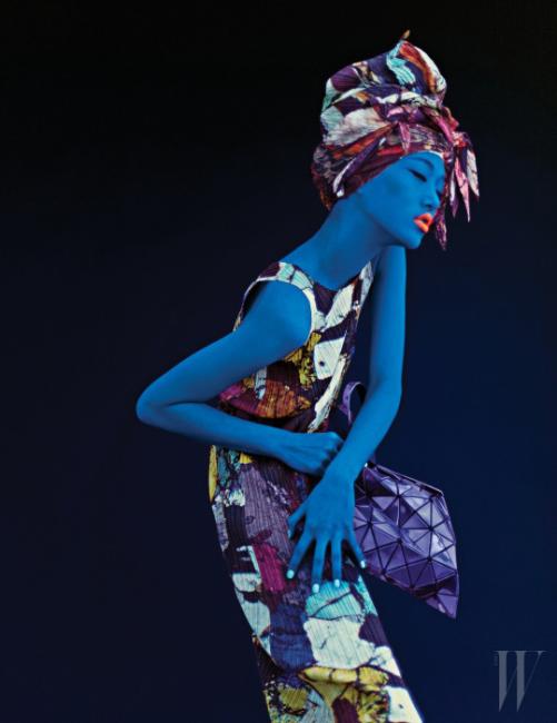 이국적인 프린트의 플리츠 드레스, 보라색 바오바오 쇼퍼백, 터번으로 연출한 추상적인 프린트의 스카프는 모두 Pleats Please 제품.