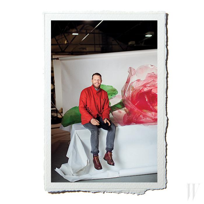 """동료 세트 디자이너 앤디 나이트의 웨어하우스에 있는 힐먼. 뒤쪽의 퍼스펙스 장미는 도버 스트리트 마켓 상하이점에서 의뢰해 만든 것. """"올드 패션의 낭만적인 심벌과 하이테크 재료 사이의 콘트라스트를 보여주고 싶었습니다."""""""
