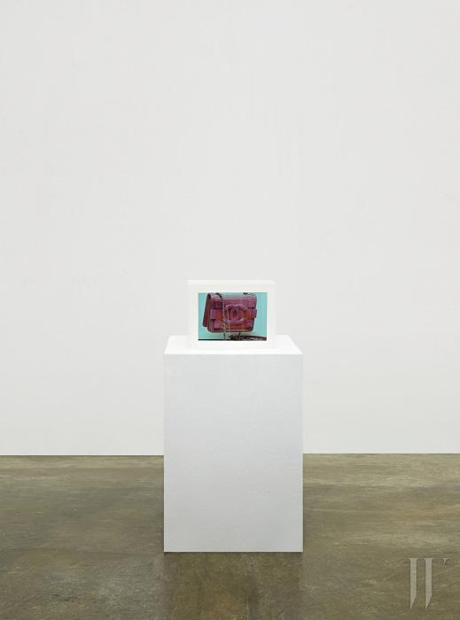 밝은 분홍색의 페이턴트 가죽과 체인이 어우러진 작은 가방은 Chanel 제품.