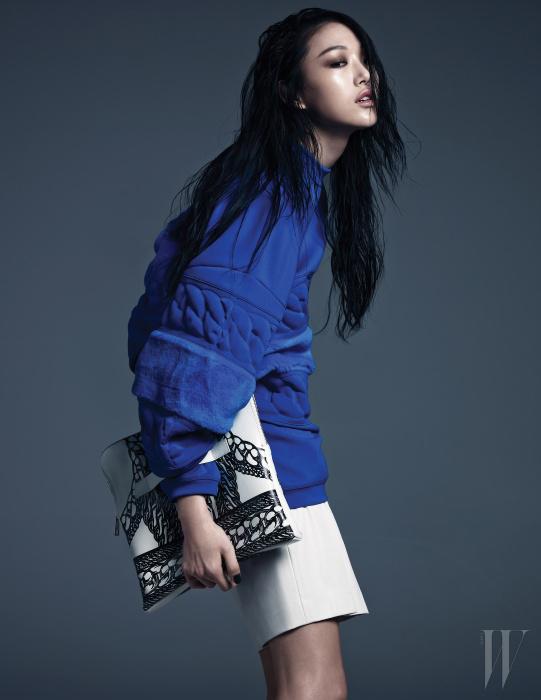짧게 깎은 퍼와 폴리에스터가 믹스된 블루 스웨트 셔츠와 주름 장식이 더해진 쇼츠는 Kye 제품.