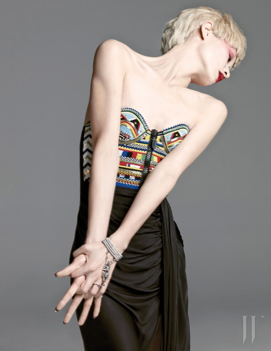 정교한 비즈 장식의 에스닉한 드레스는 Emilio Pucci, 반지와 이어진 관능적인 팔찌는 Minetani 제품.