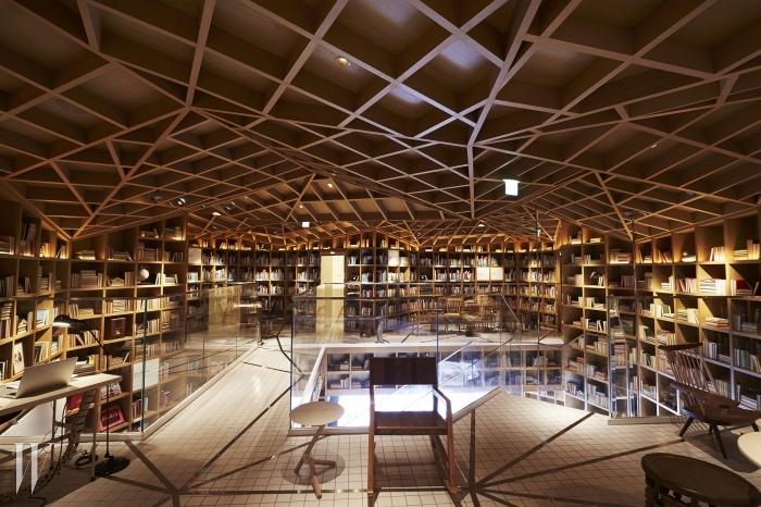 나무 책장이 천장까지 이어져 압도적이면서 아늑한 느낌을 주는 현대카드 트래블 라이브러리.