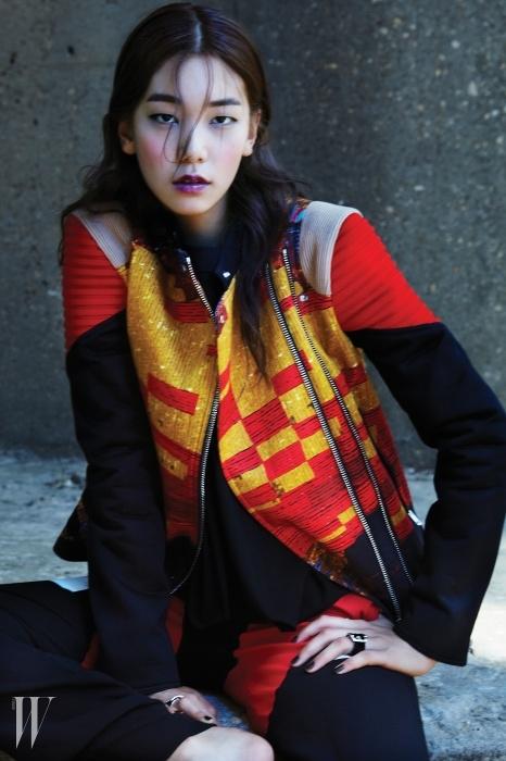 기하학적인 프린트와 강렬한 컬러 블록이 돋보이는 라이더 재킷, 검정 톱, 바우하우스풍의 밴딩 장식을 더한 팬츠, 버클 장식의 반지는 모두 지방시 by 리카르도 티시 제품.
