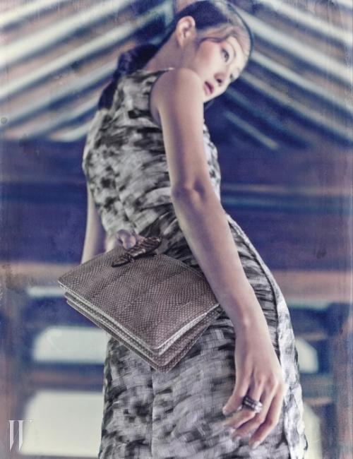 미스트 라이트 그레이 색상이 은은함을 더하며 슬림한 실루엣이 특징인 드레스, 여닫이 부분에 뱀을 연상시키는 독창적인 장식을 더한 에이어스 가죽 소재의 클러치, 조형적인 반지는 모두 Bottega Veneta 제품.