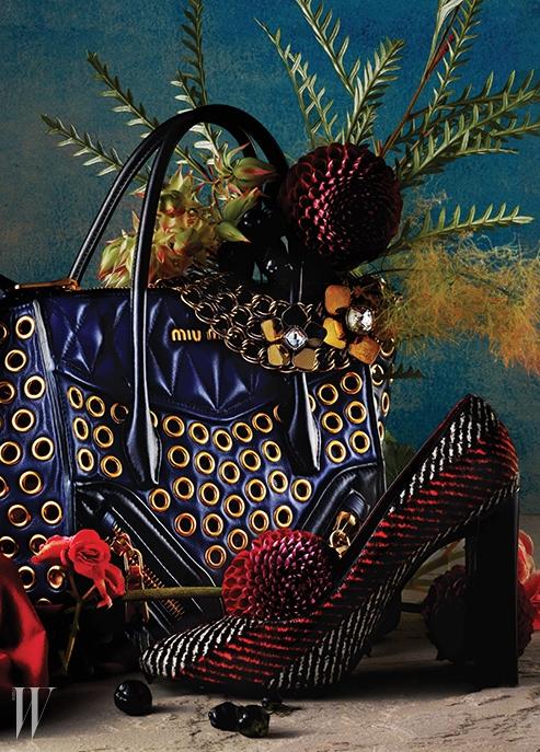 메탈 아일릿 장식의 큼직한 네이비색 나파 가죽 백은 Miu Miu, 대담한 꽃 모티프가 돋보이는 크리스털 장식의 체인 목걸이는 Fendi, 줄무늬의 트위드 소재 펌프스는 Fendi 제품.