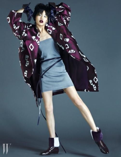 아방가르드한 볼륨과 기하학적인 무늬가 특징인 로브형 테일러드 코트, 미니 튜브톱 드레스처럼 올려 입은 니트 스커트, 얇은 가죽 벨트, 자주색 플랫 부츠와 발목에 착용한 모피 워머,가죽 장갑은 모두 Tod's 제품.