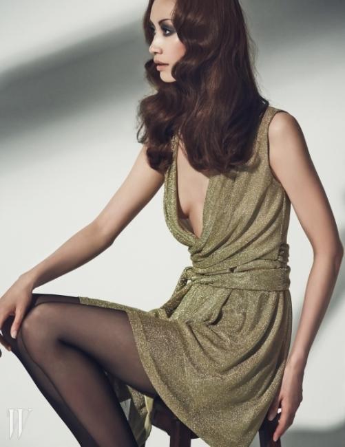 반짝이는 펄이 가미된 골드 톤의 관능적인 랩 드레스는 Diane Von Furstenberg 제품.