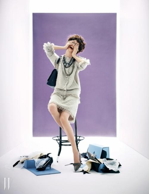 넉넉한 실루엣의 트위드 소재 재킷과 스커트, 큼직한 원석 장식 목걸이와 체인 목걸이, Love 와 You자 골드 반지, 엠보싱 효과가 돋보이는 숄더백, 모델이 신은 키튼힐 슈즈와 바닥에 놓인 검정 슈즈는 모두 Lanvin 제품.