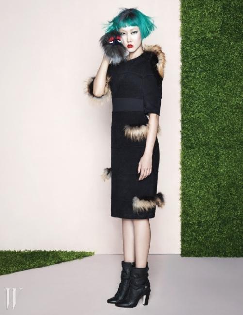 군데군데 갈색 퍼를 장식한 검정 드레스와 검은색 앵클부츠, 손에 든 퍼 장식 백버(BagBugs)는 모두 Fendi 제품.