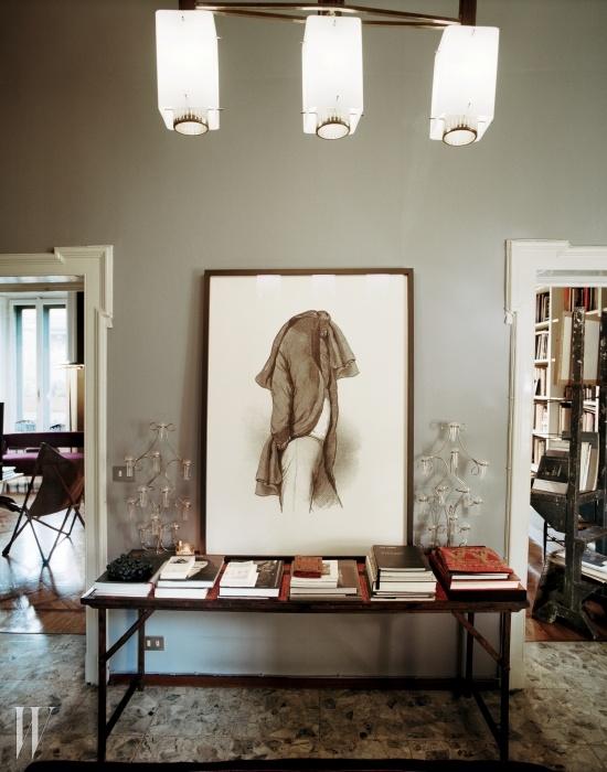 프랑스산 철과 나무로 만든 테이블 위에 놓인 마커스 스킨왈드의 작품 <Lars>(2011)와 스틸노보의 조명 장식.