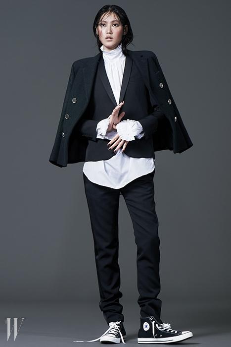 목과 소매에 러플 장식이 달린 화이트 셔츠는 드리스 반 노튼 제품. 53만원.검은색 턱시토 재킷은 4백28만원, 실크 라이닝이 들어간 검정 팬츠는 1백60만원,어깨에 걸친 은색 버튼 장식 모직 코트는 4백만원대. 모두 생로랑 제품.검은색 하이톱 스니커즈는 컨버스 제품. 5만원대.