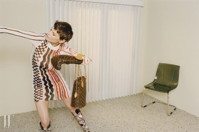 모노그램 캔버스가 돋보이는펀칭 백, 수트케이스와세트인 글러브는 Karl Lagerfeld& Louis Vuitton, 여러 무늬가들어간 니트 드레스,글래디에이터 스타일의 부츠는모두 Louis Vuitton 크루즈 제품.