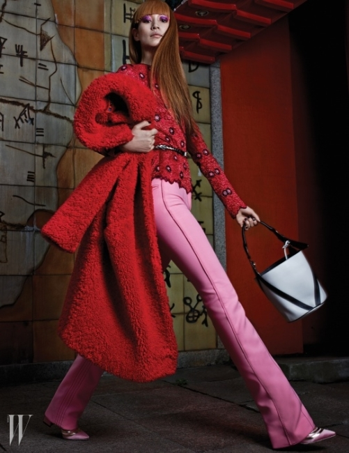 꽃무늬 패턴이 장식된레이스 톱, 분홍색 벨보텀 팬츠,새틴 소재 슈즈, 원통형 토트백은 모두Louis Vuitton, 강렬한 빨간색 모피코트는 Lucky Chouette 제품.